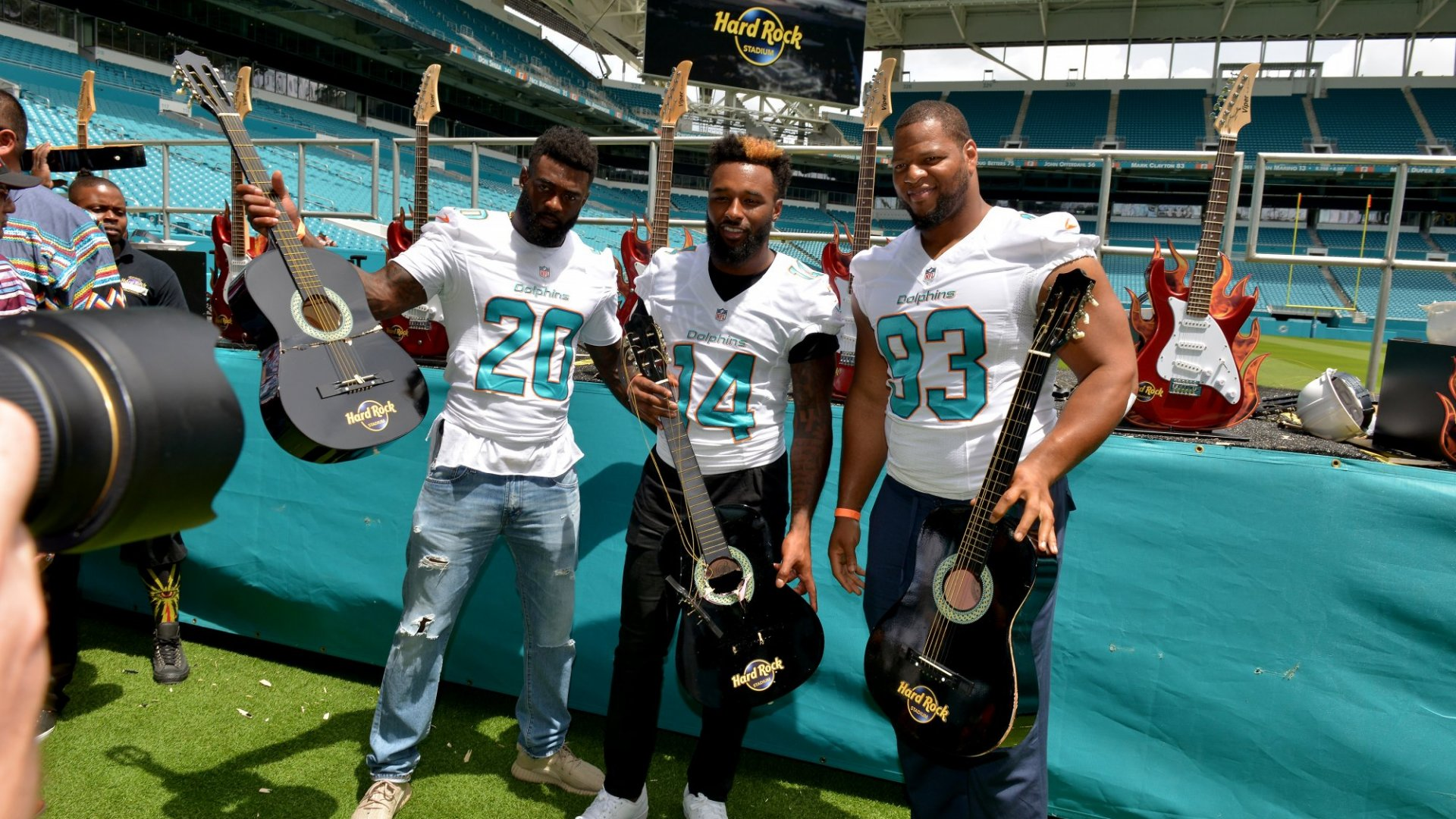 Miami Dolphins players holding Hard Rock branded guitars as the team celebrates a new stadium naming rights deal.