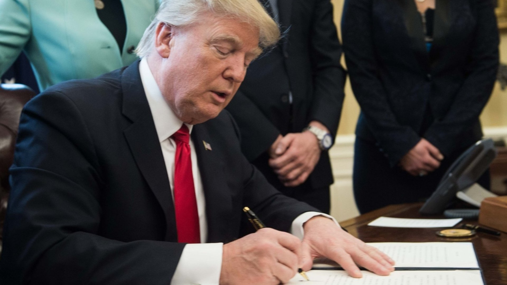 US President Donald Trump signs an executive order with small business leaders in the Oval Office at the White House in Washington, DC on January 30, 2017.
