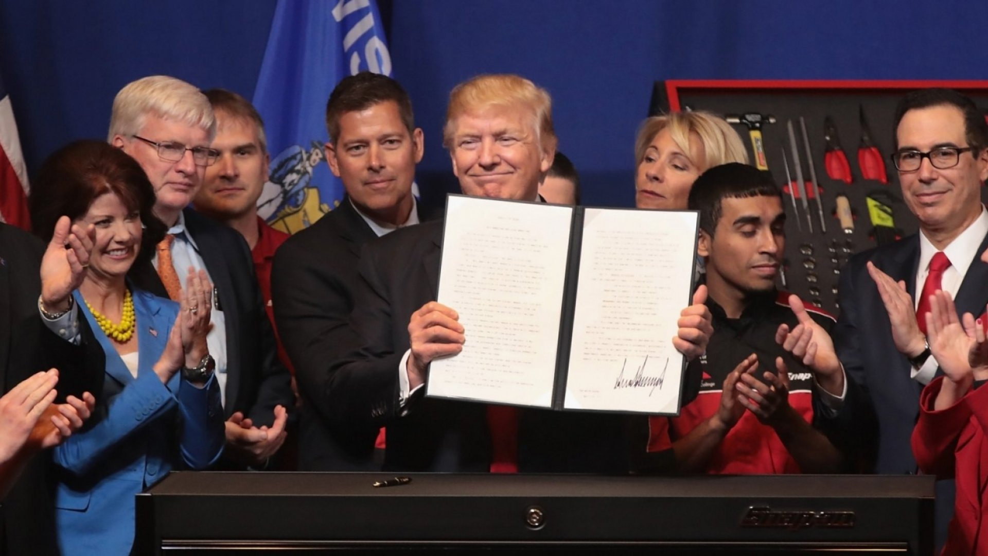 President Donald Trump signs an executive order to try to bring jobs back to American workers and revamp the H-1B visa guest worker program during a visit to the headquarters of tool manufacturer Snap-On on April 18, 2017 in Kenosha, Wisconsin.