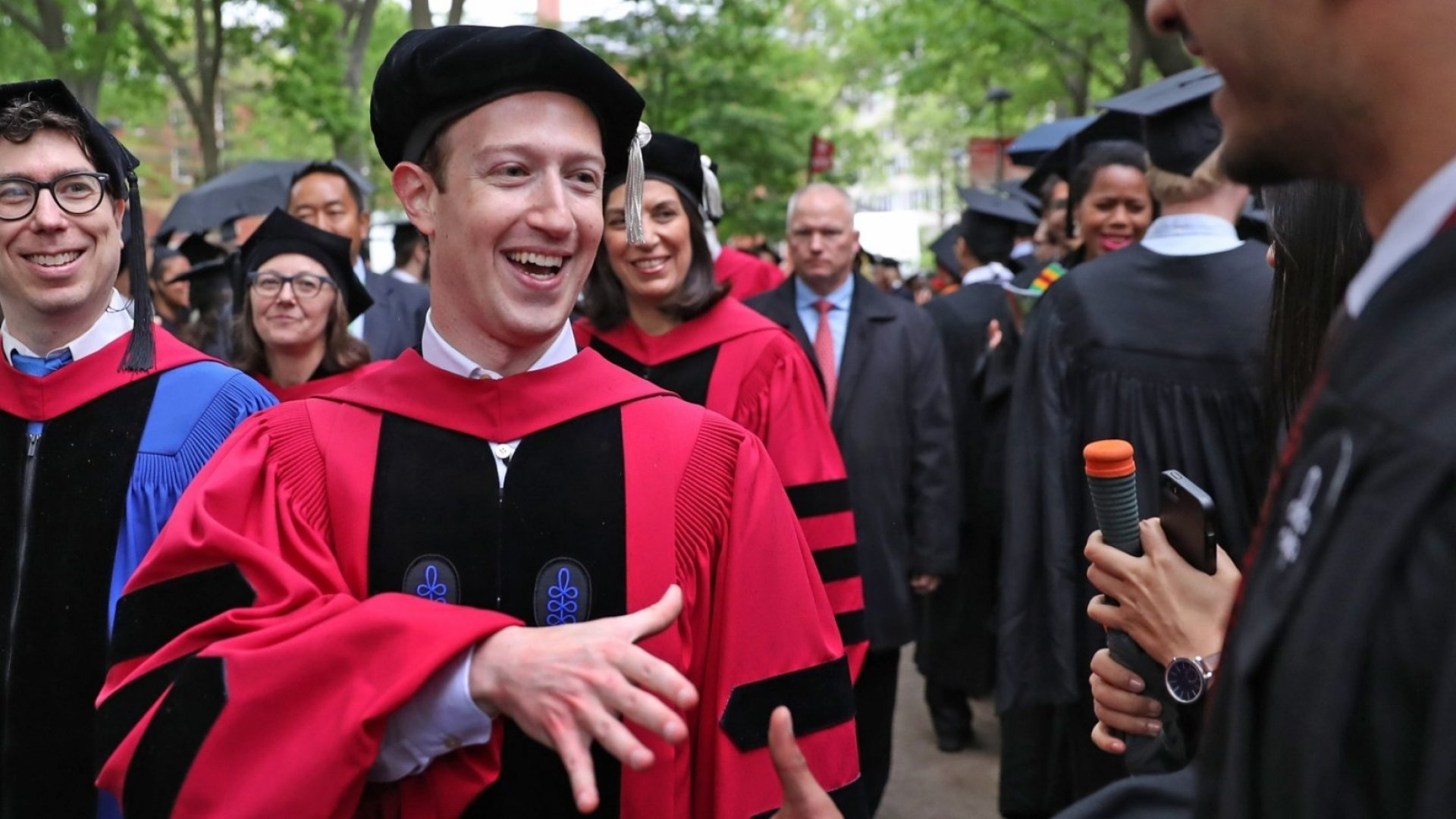 Mark Zuckerberg, Harvard dropout and CEO of Facebook, a company worth nearly $400 billion, shakes hands with graduates at the Harvard University commencement in Cambridge, Massachusetts on May 25, 2017.