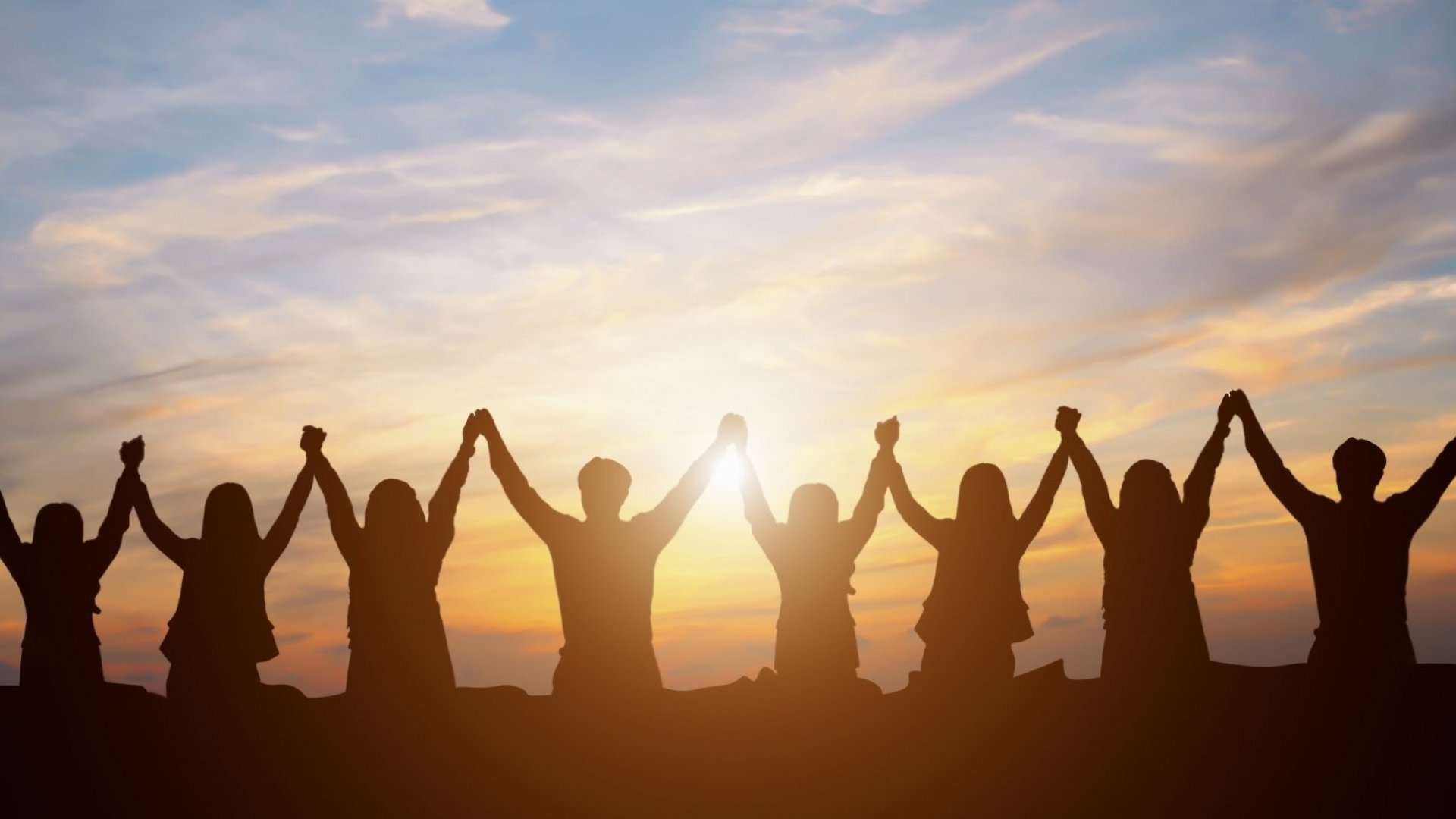 Team of people lifting hands together in front of a sunrise.
