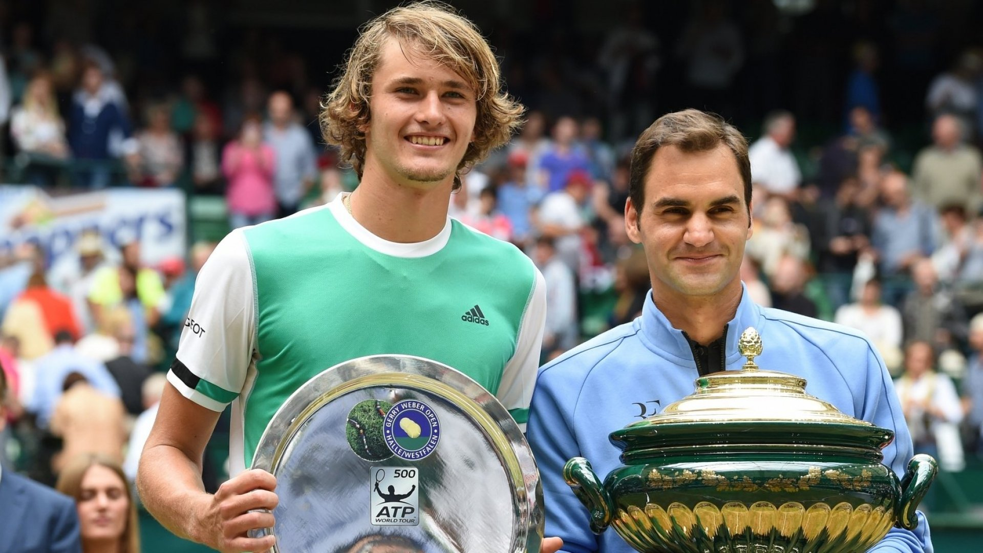 Roger Federer from Switzerland(right) poses with his trophy after winning his final match against Alexander Zverev from Germany at the Gerry Weber Open tennis tournament.