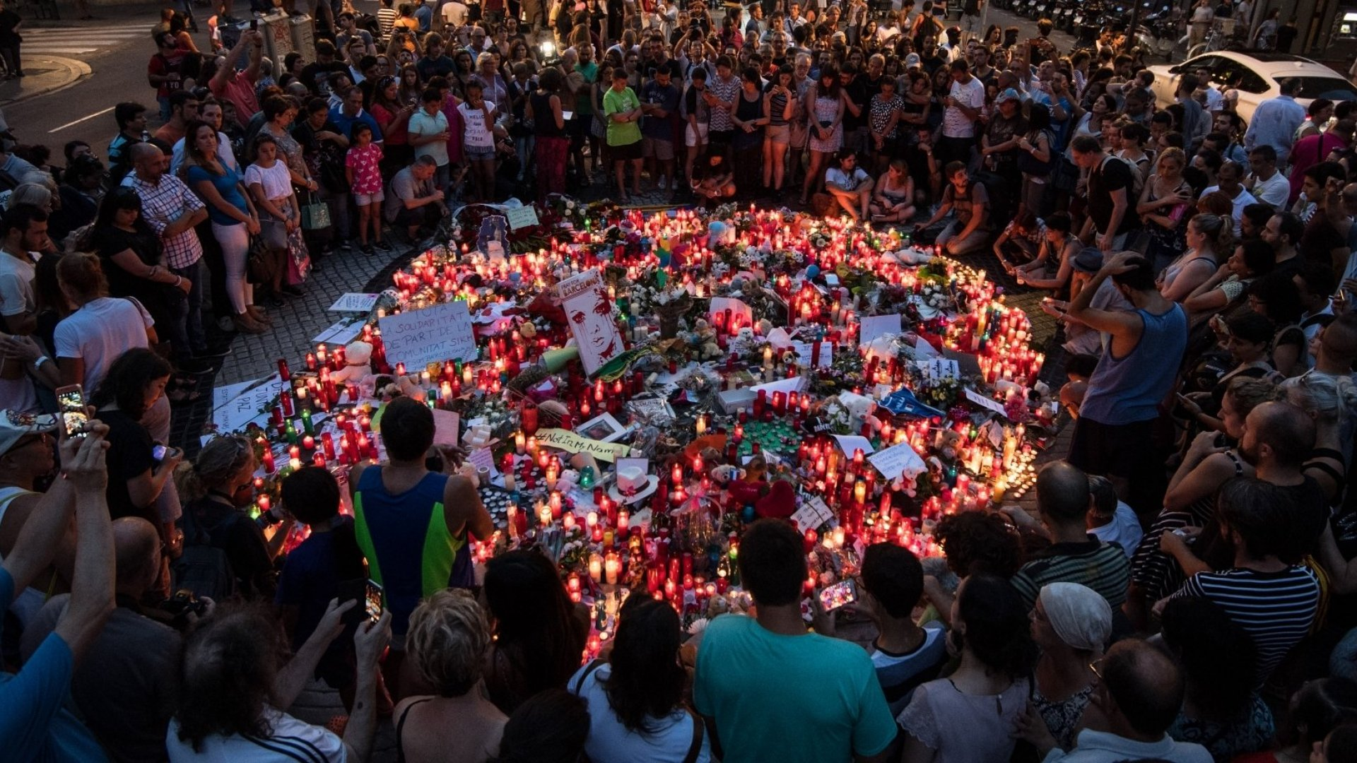 People gather around tributes laid on Las Ramblas near to the scene of a terrorist attack, on August 18, 2017 in Barcelona, Spain.