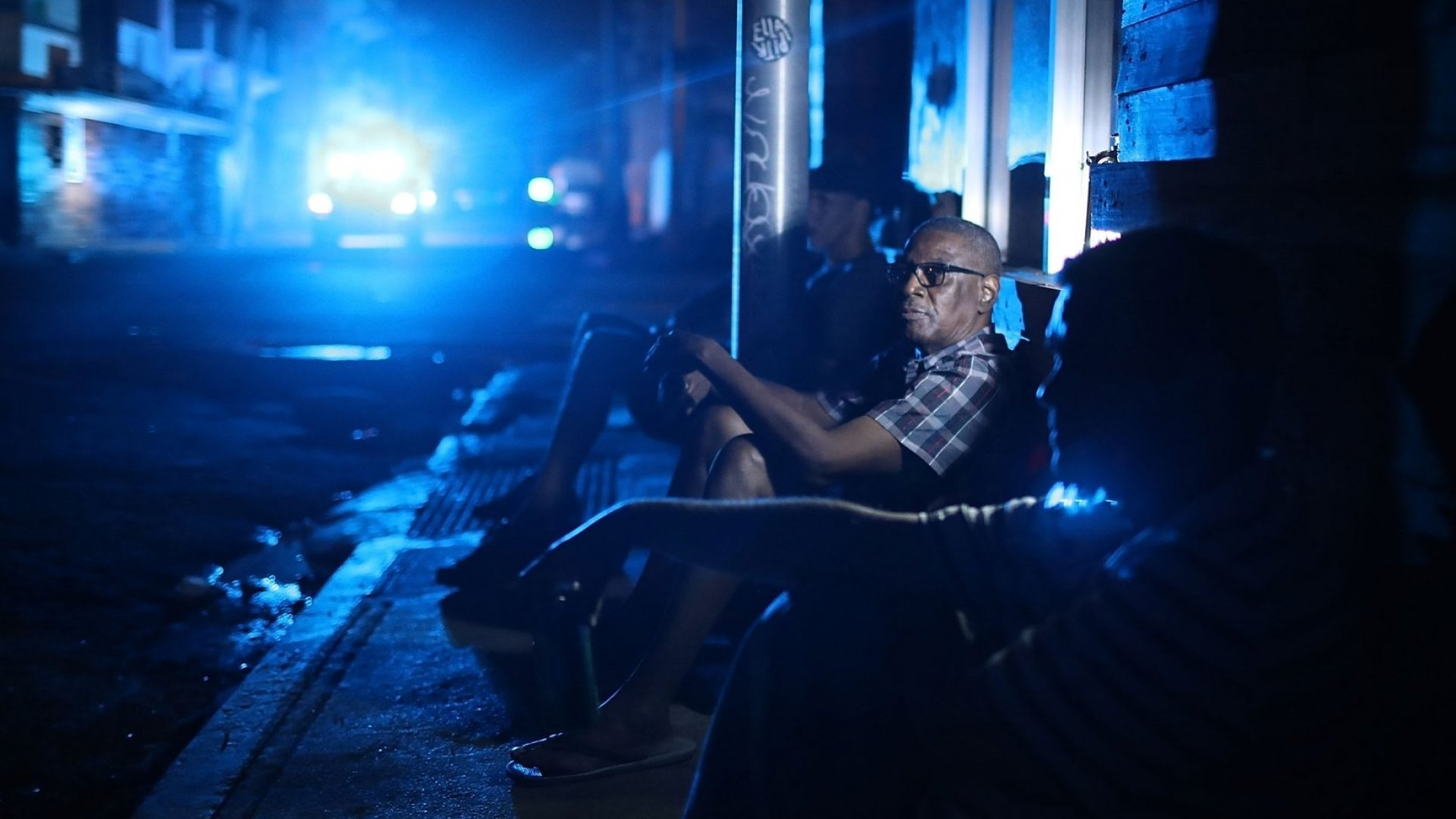 In San Juan, Puerto Rico, Jaime Degraff sits outside and tries to stay cool as people wait for the damaged electrical grid to be fixed.