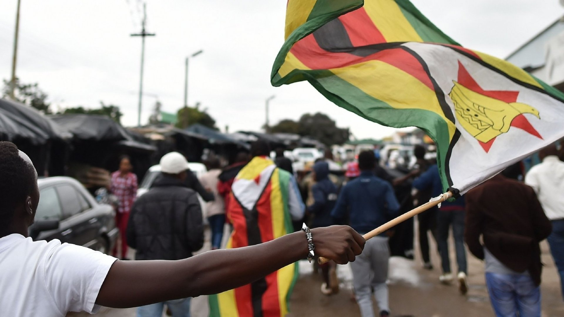 A man waves a Zimbabwean national flag during a demonstration demanding the resignation of Zimbabwe's president on November 18, 2017, in Harare.