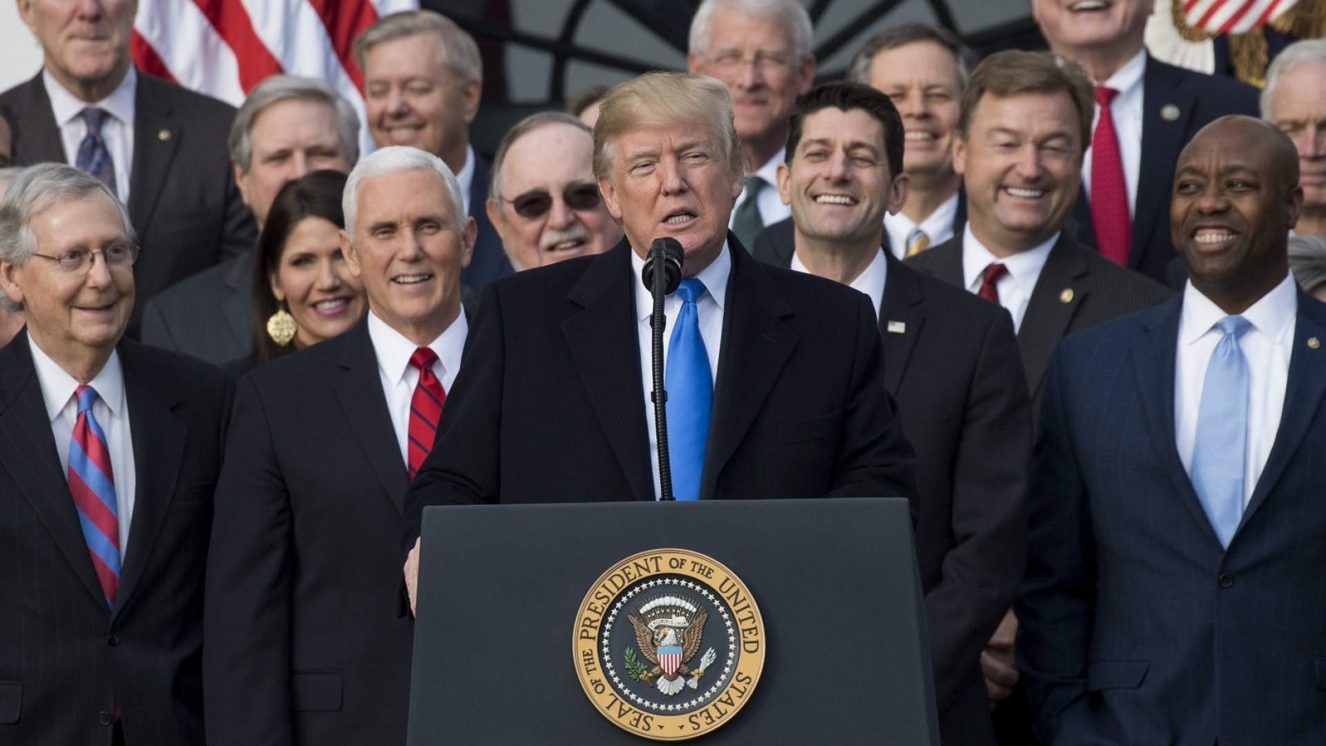 President Donald Trump flanked by Republican lawmakers speaks about the passage of tax reform legislation on the South Lawn of the White House in Washington, DC, December 20, 2017. Trump hailed a 'historic' victory Wednesday as the US Congress passed a massive Republican tax cut plan, handing the president his first major legislative achievement since taking office nearly a year ago.