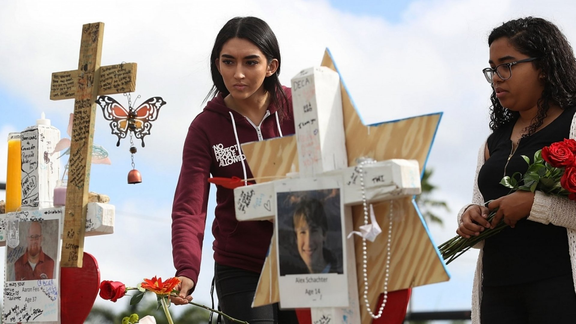 Marissa Rodriguez (left) and Ambar Ramirez visit a makeshift memorial in front of Marjory Stoneman Douglas High School for the 17 people killed there on February 14.