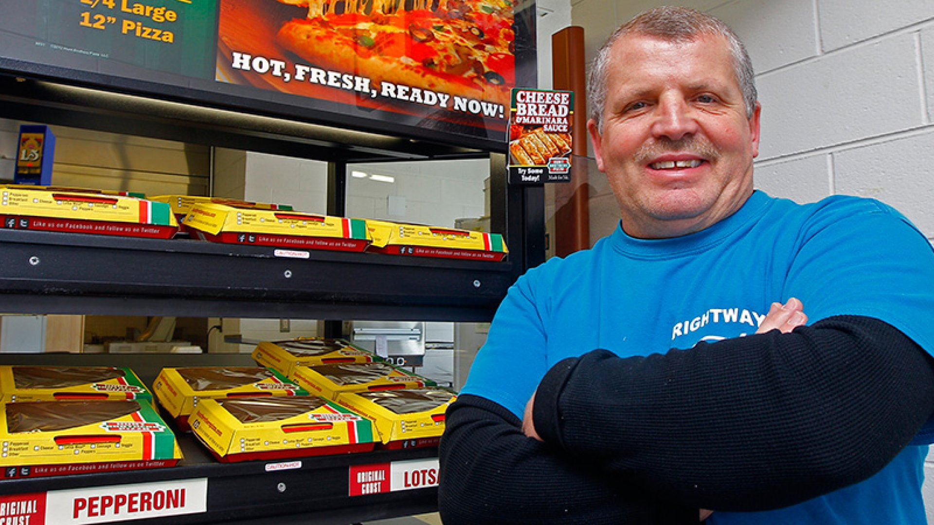 Roy Bruce, owner of the Rightway Foodmart poses for a photo in front of a Hunt Brothers Pizza display in Andersonville, Tenn. Hunt Brothers Pizza is quietly winning over the rural South by slipping into places big-name pizza chains probably couldn't survive.