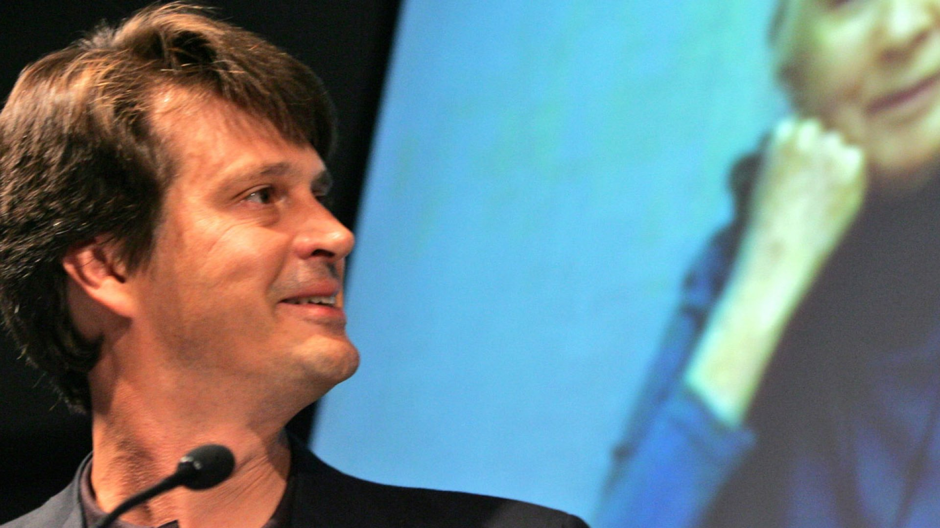 John Hanke smiles as he to London via video teleconference from Google Earth's offices in New York.