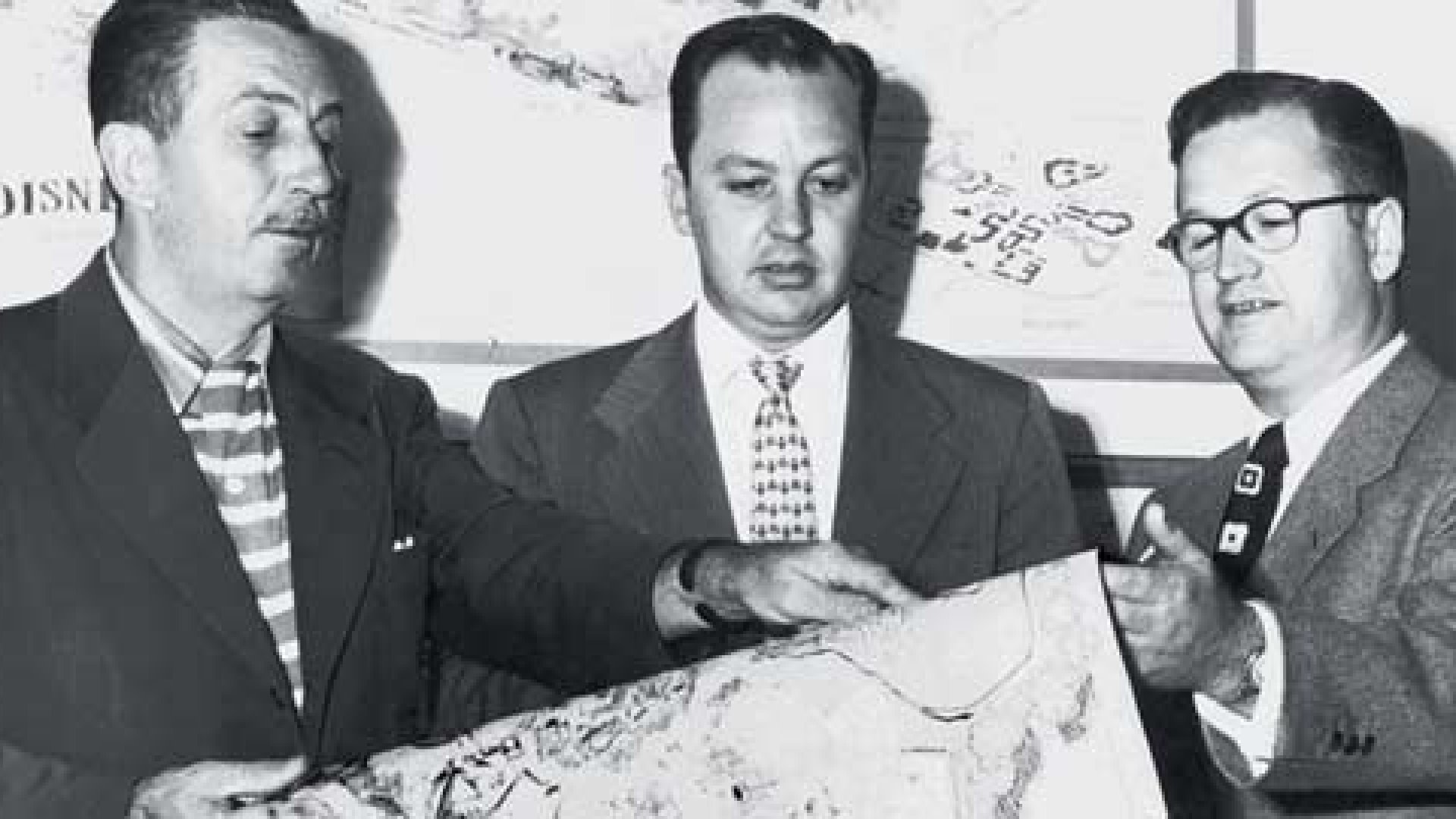 """<strong>Key to the Kingdom</strong> Harrison (""""Buzz"""") Price (far right) looks at plans for Disney World with Walt Disney (far left) and another Disney executive."""
