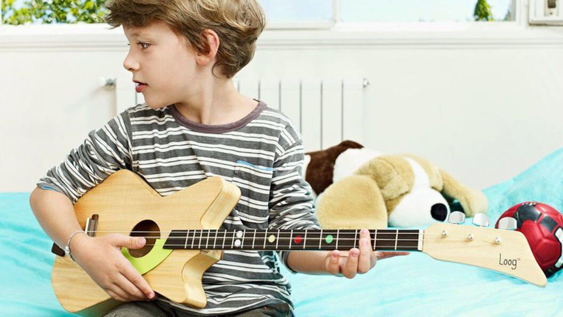 A boy plays his Loog Guitar.