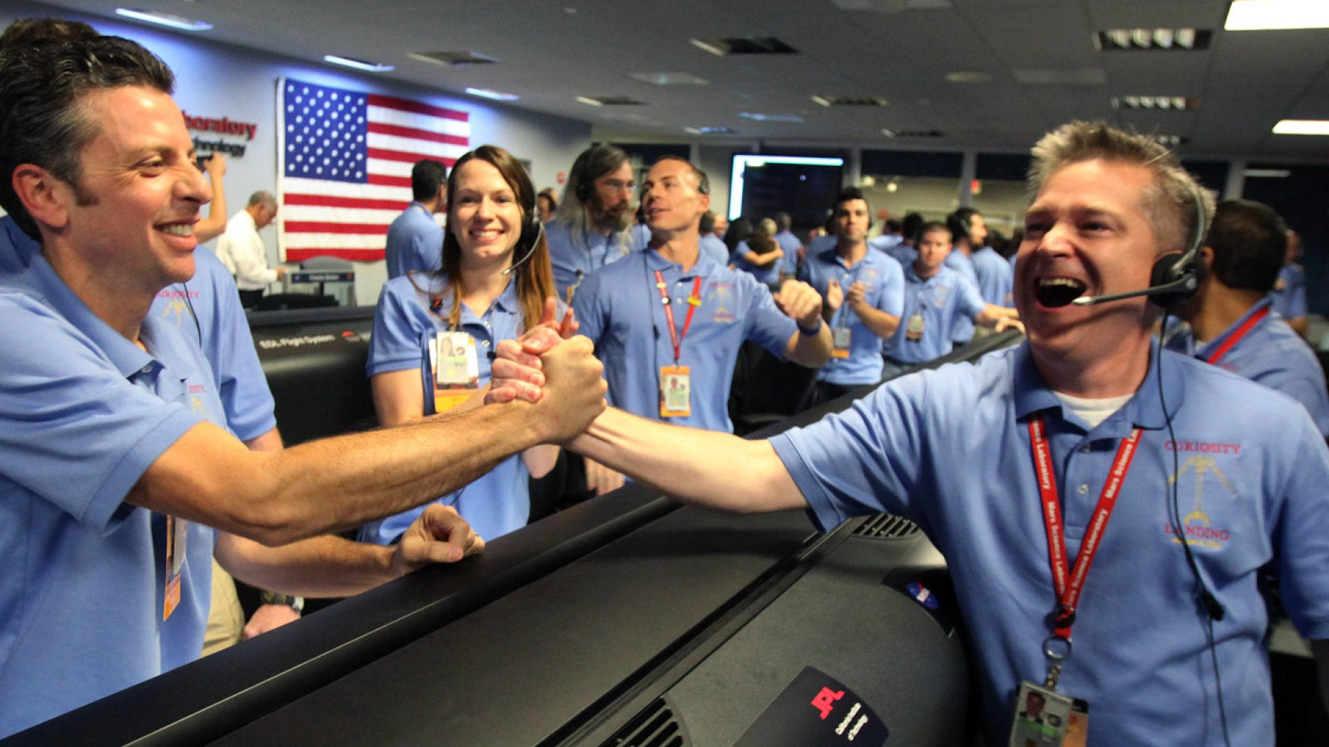 Flight director Keith Comeaux, right, celebrates with Martin Greco after a successful landing of NASA's Mars Science Laboratory Curiosity rover at Jet Propulsion Laboratory on August 5, 2012 in Pasadena, California.