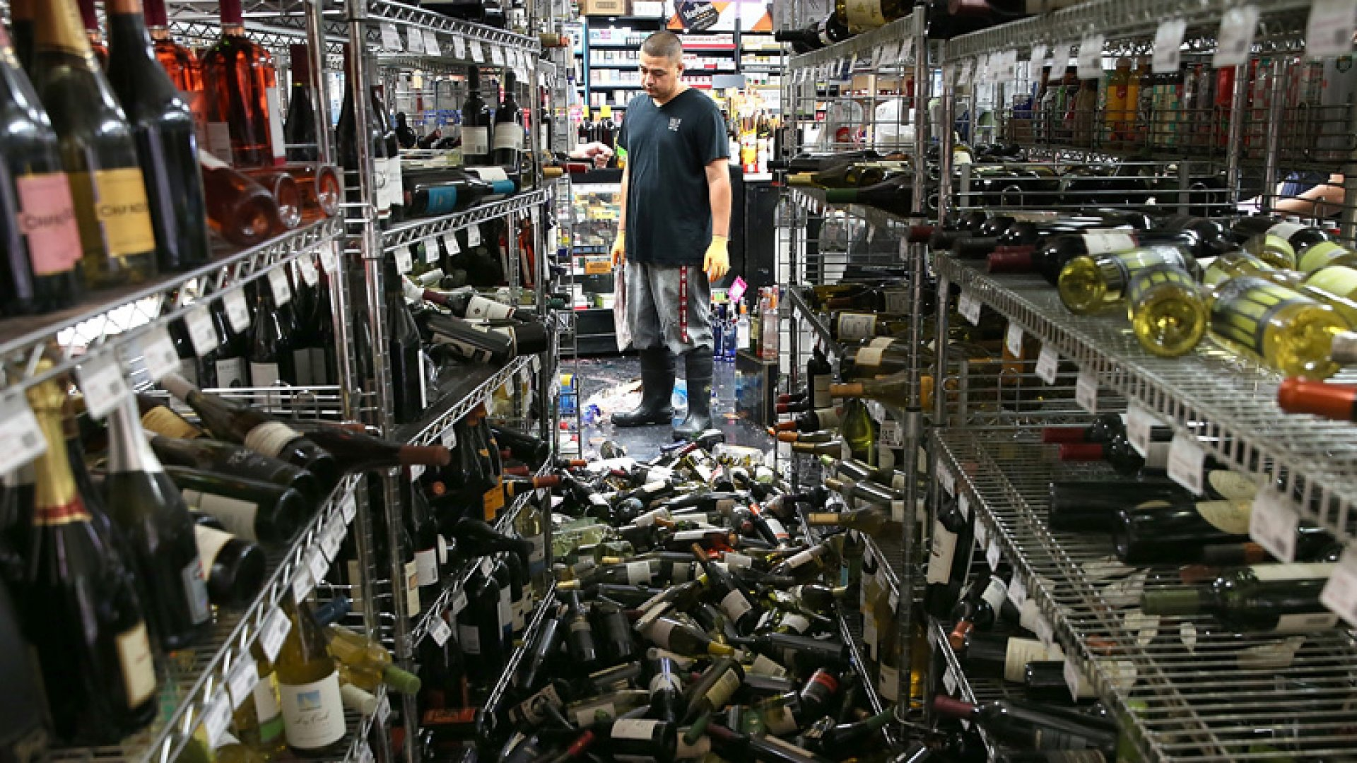 A worker looks at a pile of wine bottles that were thrown from the shelves at Van's Liquors following a reported 6.0 earthquake on Sunday.