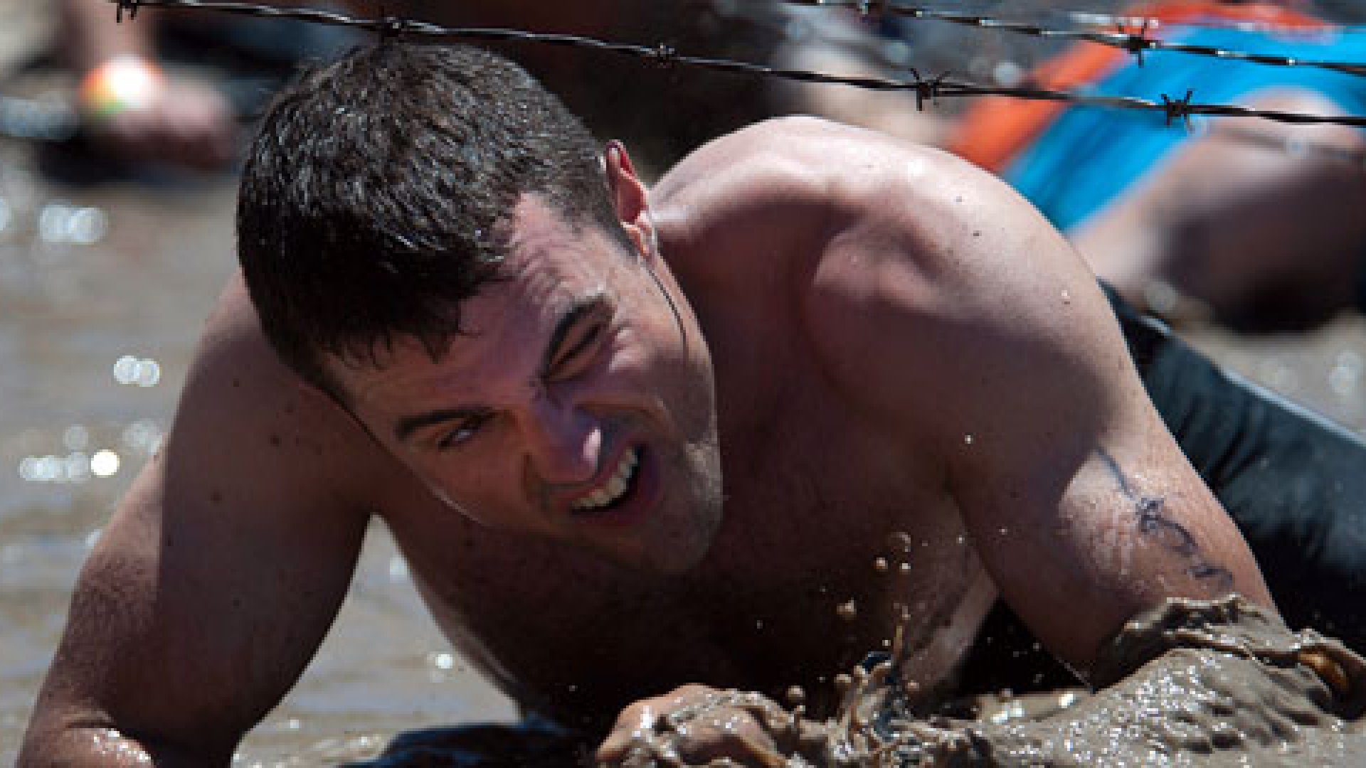 Mass Communication Specialist 3rd Class Sebastian McCormack, crawls through the mud on his way through the third obstacle of a Tough Mudder competition in Snow Valley, California.