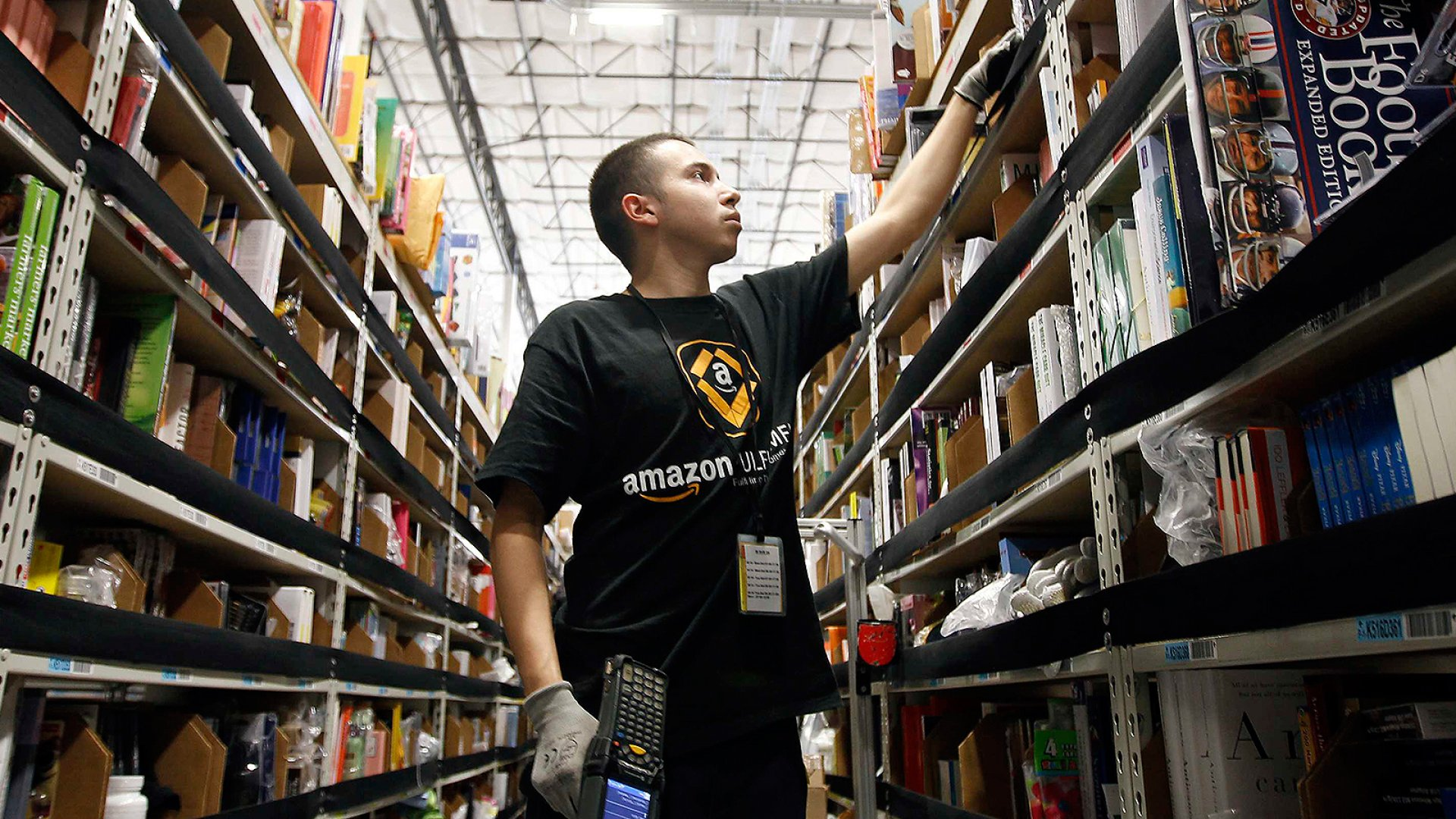 A worker gathers items for delivery from the warehouse floor at Amazon's distribution center in Phoenix.