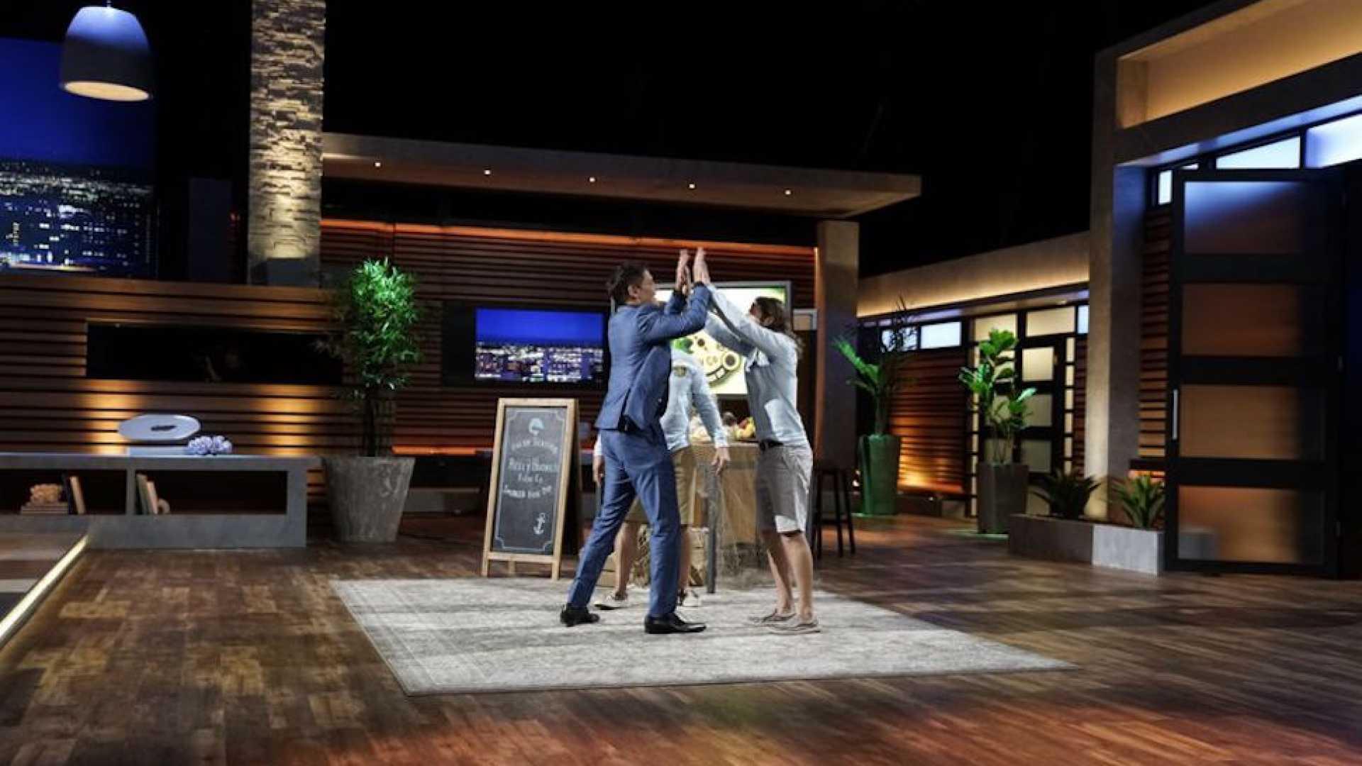 Mark Cuban celebrates with entrepreneurs Steven Markley and James Arcaro on Shark Tank.
