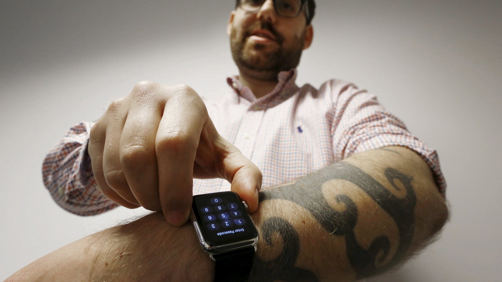 Reuters journalist Matt Siegel inputs his passcode onto his Apple Watch as his tattoos prevent the device's sensors from correctly detecting his skin, in Sydney, Australia, April 30, 2015.