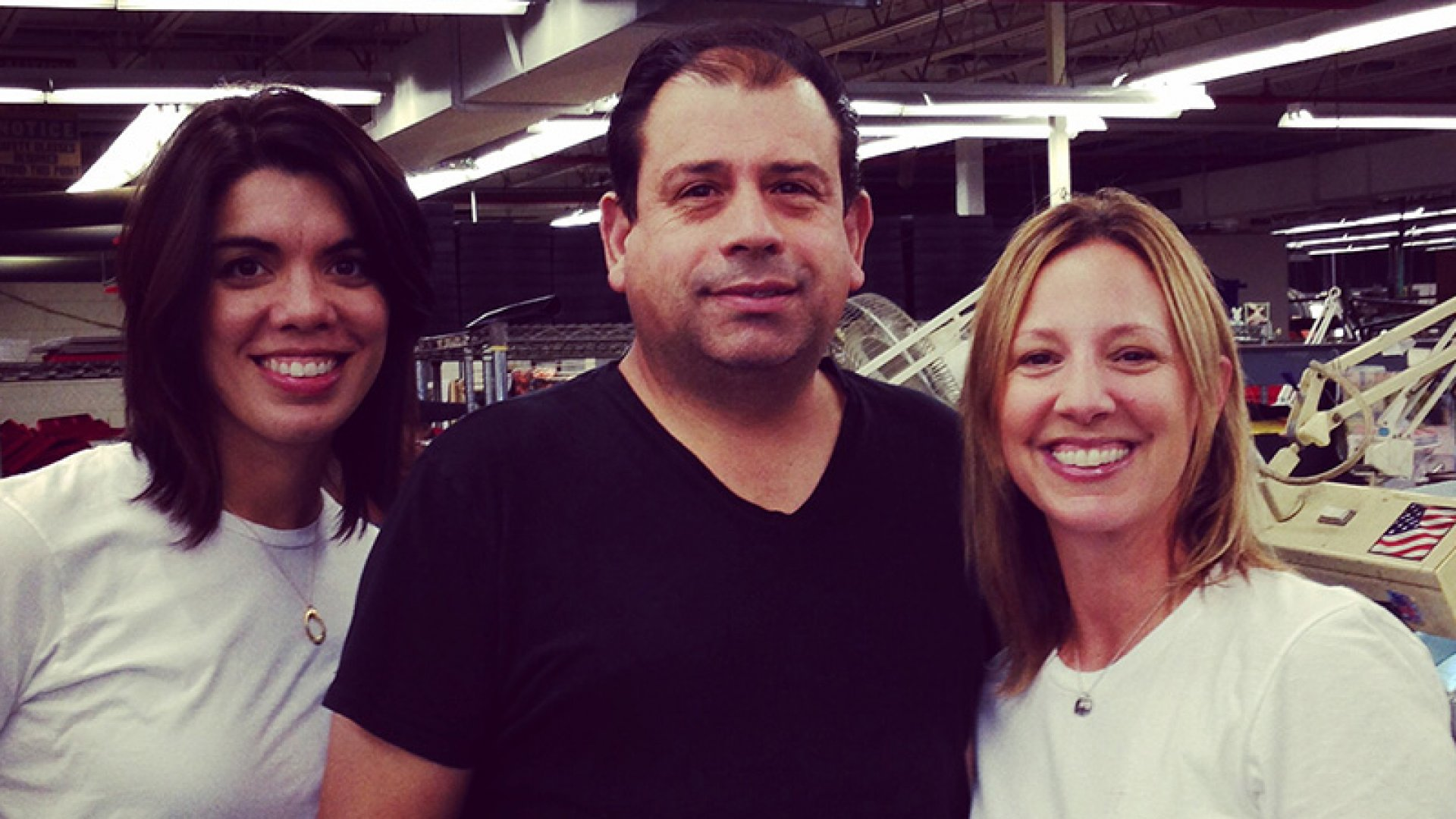 The Tiny Tags team: Director of operations Candice Kilfoyle (left) and CEO Melissa Clayton (right) flank Eduardo Viveiros, the lead emblematic polisher, at the headquarters of their manufacturing facility.