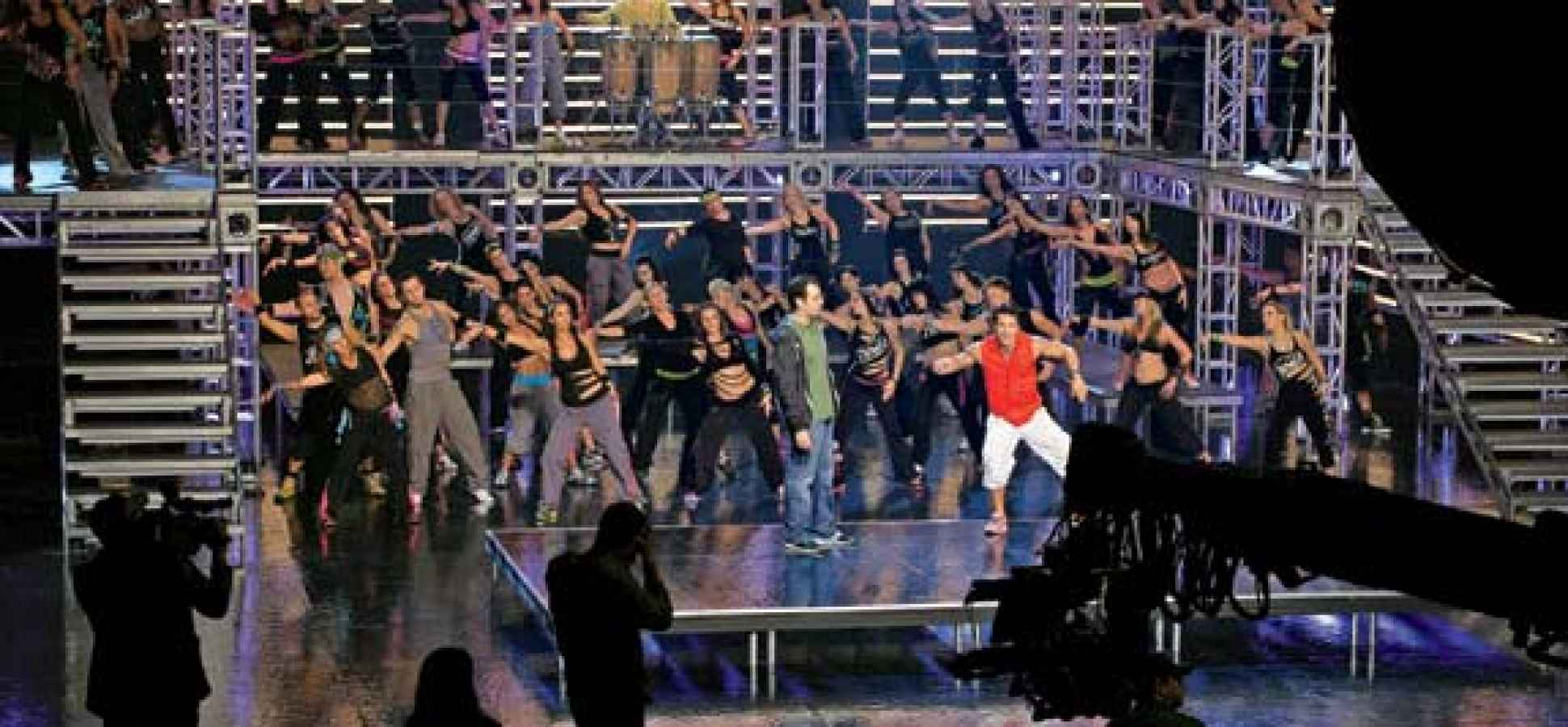 alberto beto perez in red leads a zumba video shoot onstage with him is alberto perlman