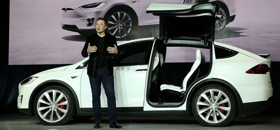 Elon Musk presenting a white Tesla Model X in a corporate event