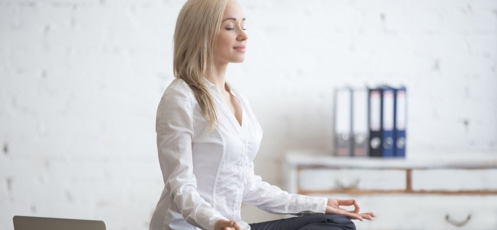 Businesswoman meditating in her office